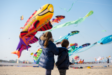 Children looking at group of colorful large kites flying in clear sky Stock Photo - 80094369