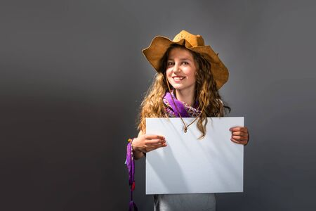 Smiling pretty cowgirl holding white board on dark background Stock Photo