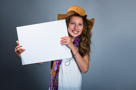 Smiling pretty cowgirl holding white board Stock Photo - 79734272