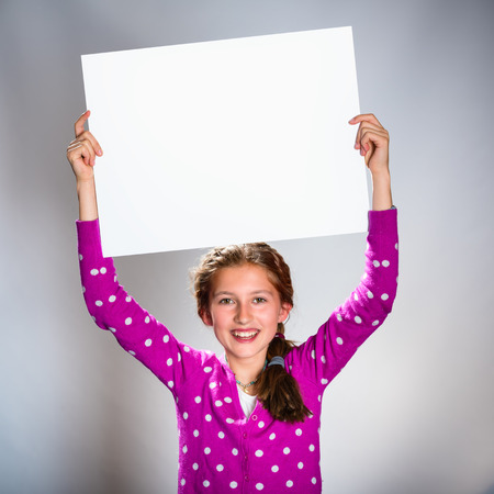 Cute teenager holding white board looking at camera Stock Photo