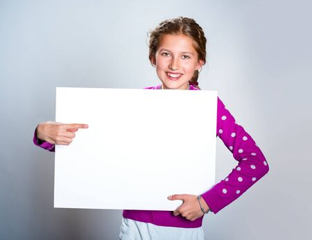 Gorgeous girl pointing at white billboard Stock Photo - 79854701