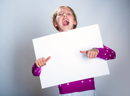 Girl looking out from the blank banner showing thumb up sign Stock Photo