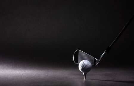 Golf ball, tee and iron on black background Stock fotó