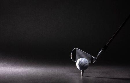 Golfball, Tee und Bügeleisen auf schwarzem Hintergrund
