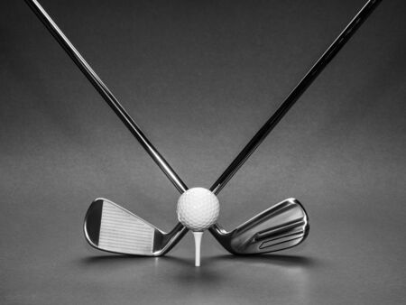 Golf clubs with ball on dark background