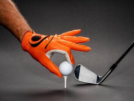 Man's hand positioning a golf ball