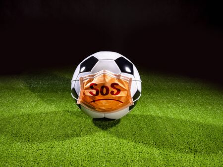 Soccer ball with mask due to air pollution or an epidemic. Protection from viruses, infections, exhaust gases and industrial emissions
