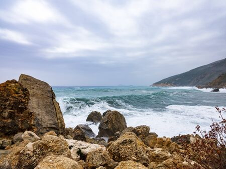 Waves hitting rocks on the Baunei coast. Background blur and with sunlight filtering from the clouds. Dramatic natural background. Stock Photo