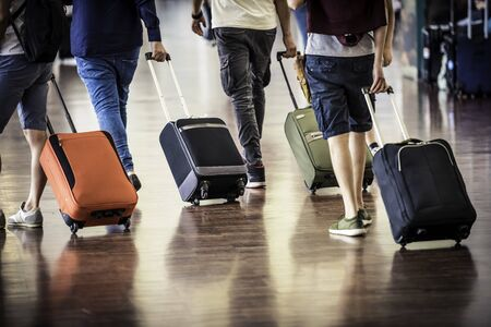 Travelers with suitcases walking through the airport  写真素材