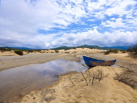 Wild sardinian coastal seascape with a wooden, old blue boat on golden beach Stock fotó