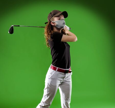 Close-up of a girl playing golf with golf club and protection mask isolated on green background