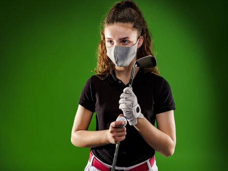 Closeup of a girl playing golf with the coronavirus protection mask