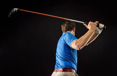 Close-up of a golf player perfecting the swing isolated on dark background