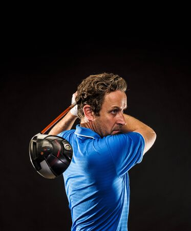 Portrait of a golf player perfecting the swing isolated on dark background, vertical image Stock fotó