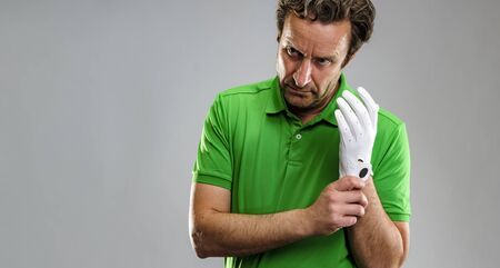 Closeup of a male golfer put on a glove. Horizontal format over a gray background. Stock fotó