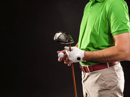 Closeup of a male golfer holding a golf ball, a golf iron and wearing a white golf glove. Horizontal format over a black background.