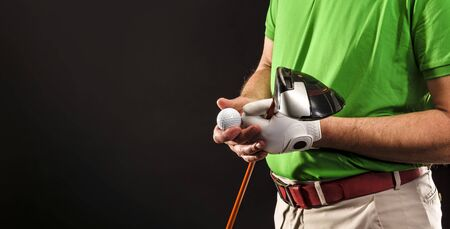 Close-up of a golfer with golf club, golf ball and glove before pulling
