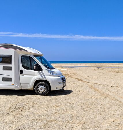 Camper van parked on a beach in wonderful oasis of Piscinas, with imposing and sinuous dunes of fine, warm and golden sand Stock fotó