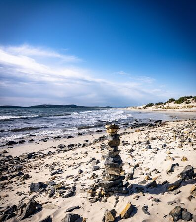 Stack of pebbles stone on the beach of Porto Pino, Sant'Anna Arresi, Sardinia, Italy. Background for balance, meditation and zen theme. Фото со стока