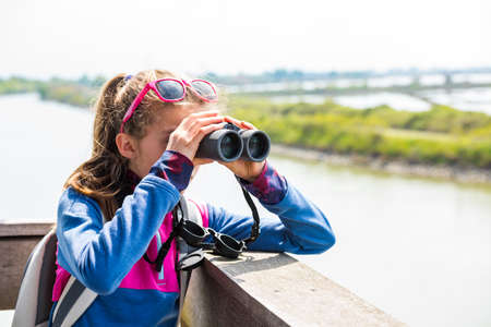 Young girl watching through binoculars from a wooden birdwatching cabin at nature reserve. Observation of birds. Birdwatching. Banco de Imagens