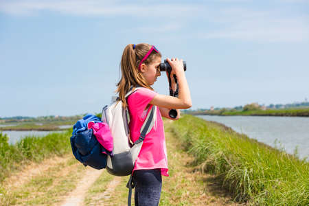 Young girl watching through binoculars against the background of the nature. Observation of birds. Birdwatching