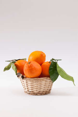 A wicker basket full of fresh orange fruits, isolated on a white background. Citrus fruit and healthy food concept.