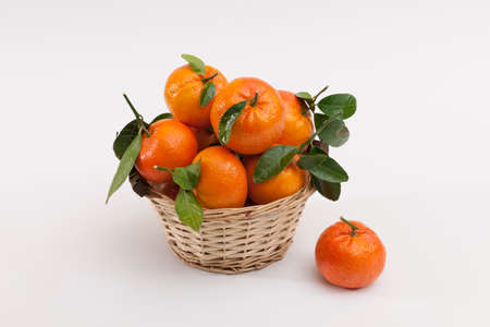 A wicker basket full of fresh tangerine fruits, isolated on a white background. Citrus fruit and healthy food concept.