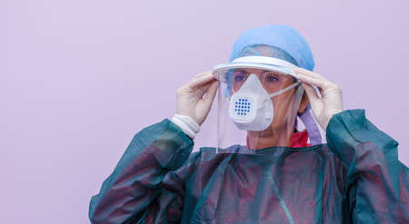 A female doctor in a hospital ward protects herself from the covid-19 virus with a protective plexiglass mask, a mask with a filter, a hair cap and a disposable gown.