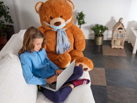 Child takes lessons from home with his laptop, sitting on the sofa with his teddy bear wearing the mask to protect himself from the coronavirus
