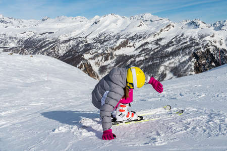 Young woman skier getting up after the fall on mountain slope. Ski resort at Alpe Devero, Piedmont, Italy. Winter sports concept. Stock fotó