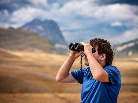 Portrait of a man standing on a mountain hill and looking into the binoculars in the distance, Campo Imperatore, Gran Sasso National Park, Abruzzo region, Italy. Travel concept. Looking to the future
