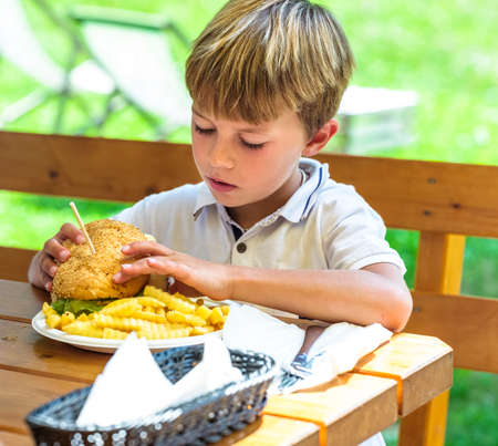 Tasty hamburger with fries eaten by a child on a sunny day.