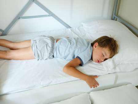 Child in pajamas sleeping in his bed without blankets, illuminated by the light that filters through the window