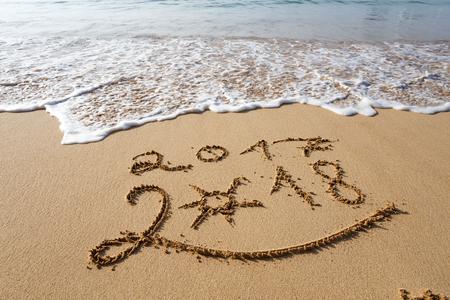 새해 복 많이 받으러 2018 년 해변에서 레터링하기. 스톡 콘텐츠