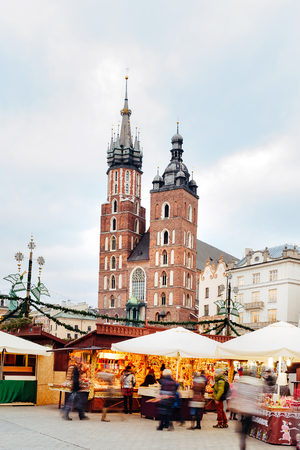 assumed: Fantastic view of the Christmas, New Years Fair in KRAKOW. Main Market Square and St. Marys Basilica (Church of Our Lady Assumed into Heaven) in the evening. Stock Photo