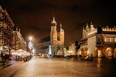 Fantastic view of the Christmas, New Years Fair in KRAKOW. Main Market Square and St. Marys Basilica (Church of Our Lady Assumed into Heaven) in the evening. Stock Photo