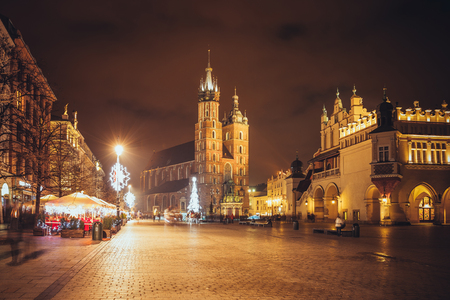 Fantastic view of the Christmas, New Years Fair in KRAKOW. Main Market Square and St. Marys Basilica (Church of Our Lady Assumed into Heaven) in the evening. Krakow, Poland, Europe Stock Photo