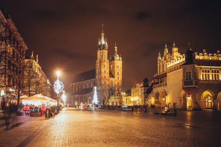 Fantastischer Blick auf die Weihnachts-, Neujahrsmesse in KRAKOW. Hauptmarktplatz und Mariä-Basilika (Kirche Unserer Lieben Frau in den Himmel angenommen) am Abend. Krakau, Polen, Europa Standard-Bild - 84155064