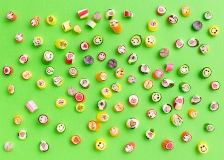 Pattern lollipops, candy on colorful green background, top view flat lay. Concepts about decoration, food background Stock Photo