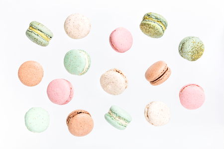 Colorful macarons cake, top view flat lay, fly falling sweet macaroon on color white isolated background. Minimal concepts falling macaroons pattern above, food background