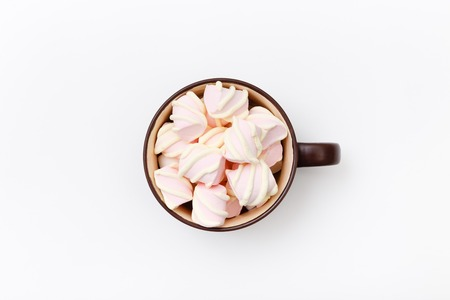 Sweet marshmallow in cup, candy on white background, top view flat lay. Isolated minimal concept above decoration, view white marshmallow, food background Stock Photo