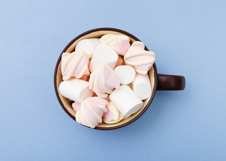 Sweet marshmallow in cup, candy on blue background, top view flat lay. Isolated minimal concept above decoration, view white marshmallow, food background