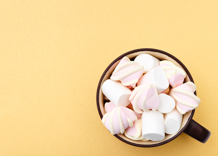 Sweet marshmallow in cup, candy on yellow background, top view flat lay. Isolated minimal concept above decoration, view white marshmallow, food background Stock Photo