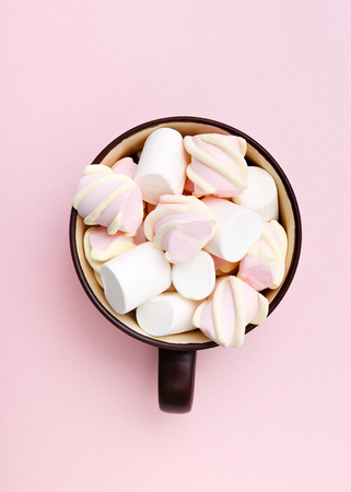 Sweet marshmallow in cup, candy on pink background, top view flat lay. Isolated minimal concept above decoration, view white marshmallow, food background