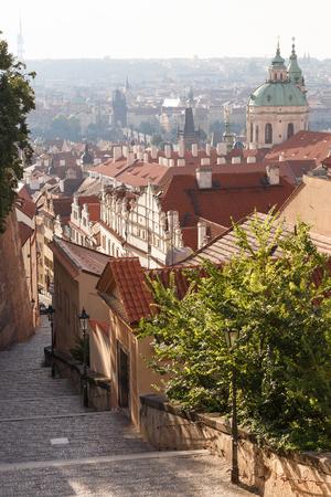 Castle stairs, view of Charles Bridge, St. Nicholas Church in Prague, Czech Republic