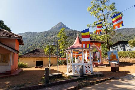 Sri Lanka, Southern Asia - February 14, 2016: Buddhist monk sitting beside the road to the mountain Adams Peak in Sri Lanka