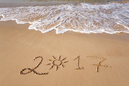 Happy New Year 2017 lettering on the beach