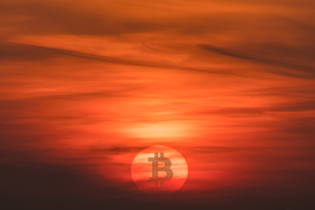Sunset with crypto currency Bitcoin symbol on the Sun. Falling currency concept.