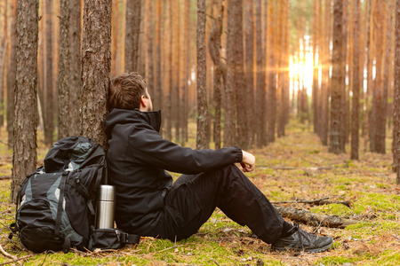 Tired tourist is resting in the forest. Traveler man at halt. Copy space Stock Photo