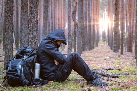 Frozen tired traveler man at halt. Tourist is resting in the forest. Copy space